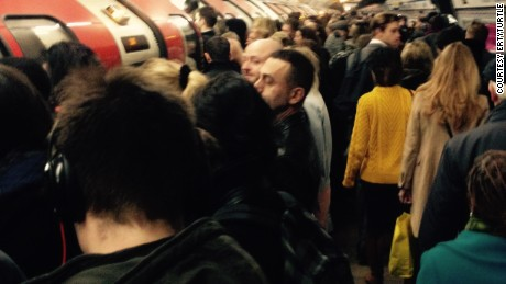 Commuters wait at a packed tube station in London.