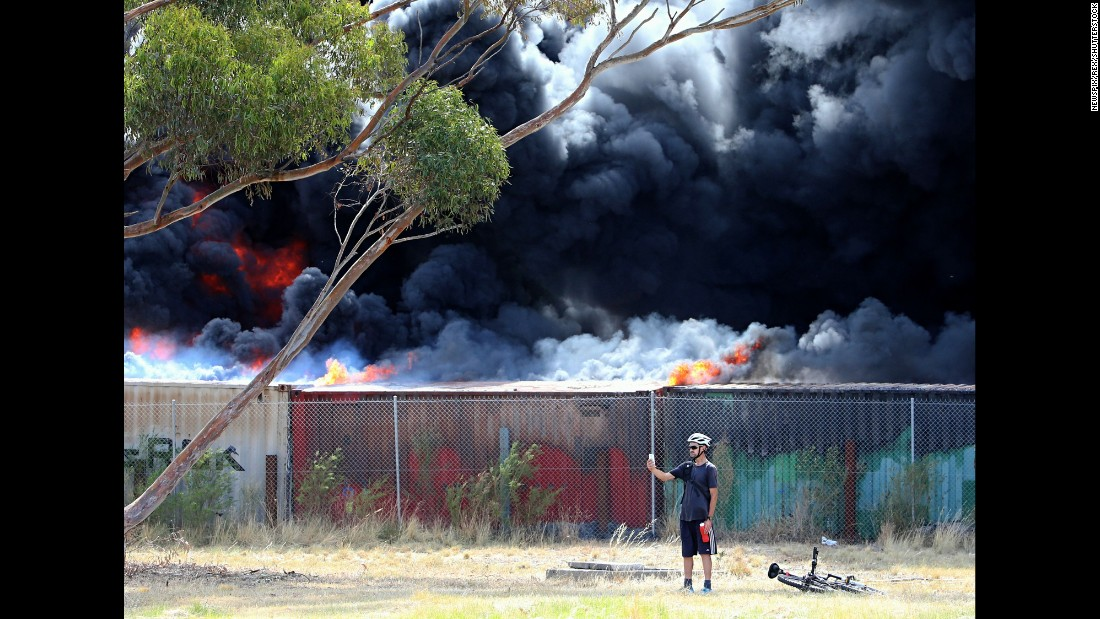 A cyclist stops to take a selfie as tires burn at a recycling plant in Melbourne on Monday, January 11.