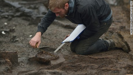 Wood specialist Mike Bamforth examining the base of a Bronze Age wooden bucket.
