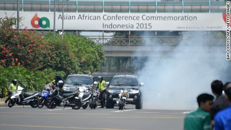 Police hide behind vehicles during an exchange of gunfire with suspects hiding near a Starbucks cafe when another blast happens in Jakarta on January 14, 2016.=