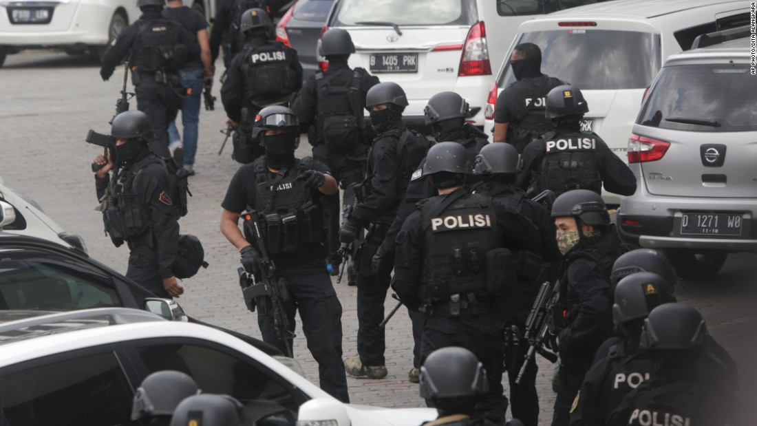 Police officers are deployed near the site where a series of blasts rocked downtown Jakarta on January 14.
