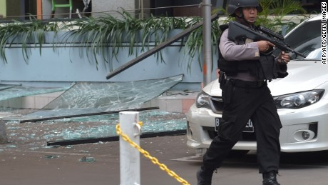 "An Indonesian anti-terror policeman walks next to the Starbucks cafe after several blasts and shootings in Jakarta on January 14, 2016.  Gunfire and explosions in the Indonesian capital Jakarta killed at least six people on January 14 in what the country's president dubbed ""acts of terror"", with fears that militants were still on the run. Starbucks announced in a statement that the company was closing all of its Jakarta branches ""until further notice"" after one of its stores in the Indonesian capital was hit by apparent suicide attacks.  / AFP/AFP/Getty Images"