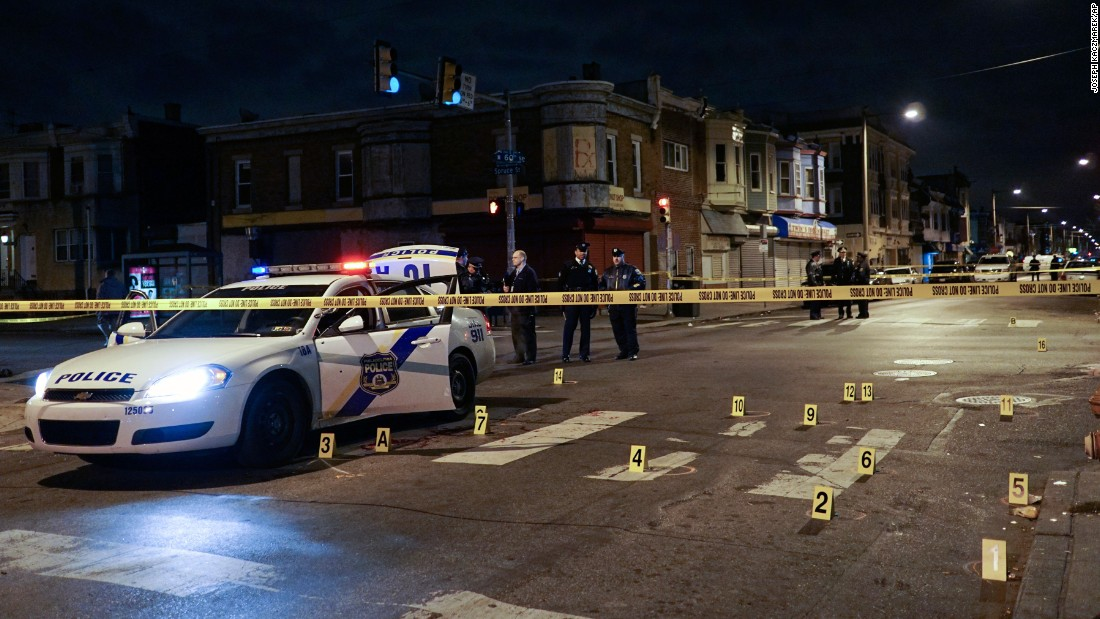"Police officers investigate the scene of a shooting Friday, January 8, in Philadelphia. Officer Jesse Hartnett was sitting in his police cruiser <a href=""http://www.cnn.com/2016/01/09/us/philadelphia-police-officer-shot/"" target=""_blank"">when he was shot multiple times</a> by a man who ambushed him, authorities said. Hartnett survived despite being hit three times at close range. A suspect was taken into custody."