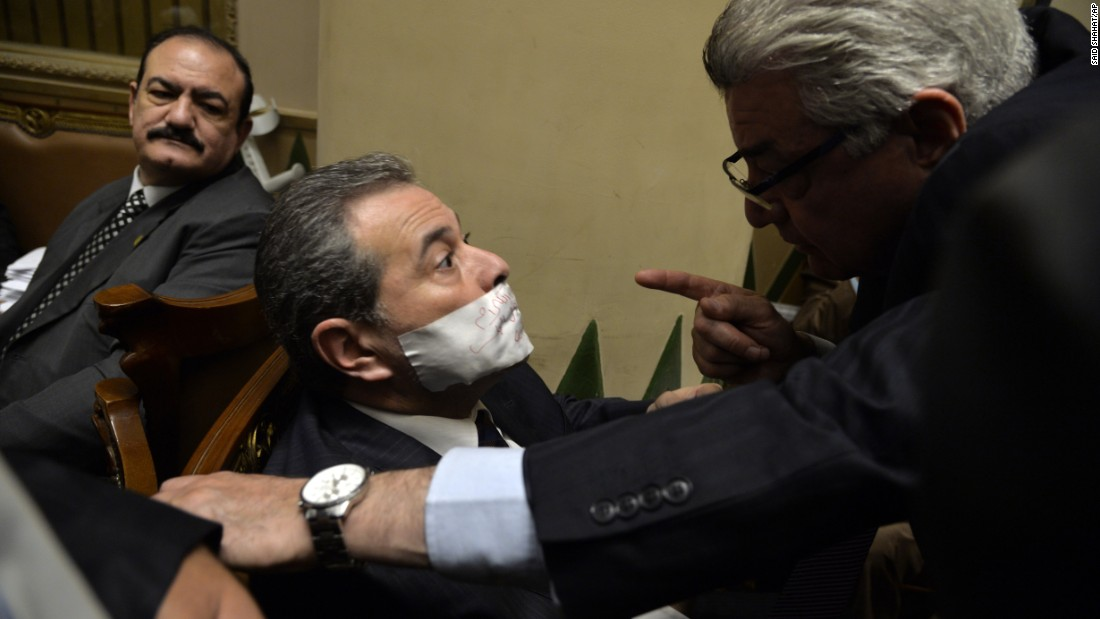 Tawfiq Okasha, a television anchorman who was elected to Egypt's Parliament, is reprimanded by a fellow legislator after taping his mouth shut in protest on Tuesday, January 12. Okasha was upset that he had not been given the floor during a parliamentary session.