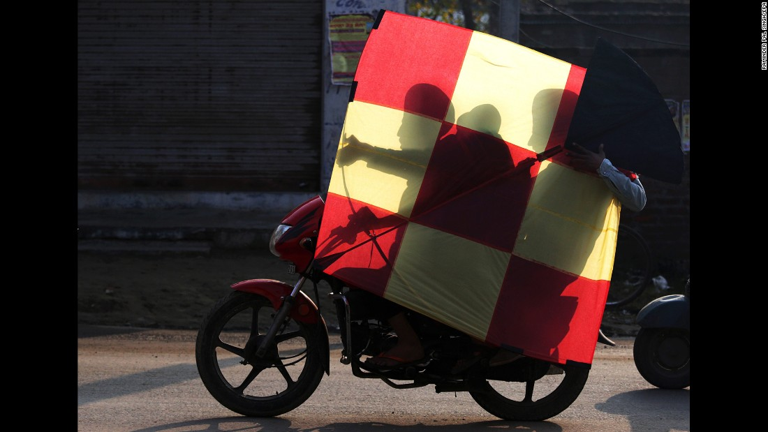 People in Amritsar, India, carry an oversized kite on a bicycle during the Lohri festival on Wednesday, January 13.