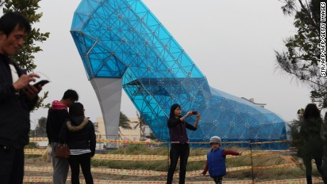 TOPSHOT - Tourists take pictures in front of a shoe-shaped church in southern Chiayi on January 11, 2016. The church, which measures 55 feet tall and 36 feet wide, took two months to build. Members of the public will be able to visit the exterior of the church before it is officially opened on February 8, 2018, before the lunar new year.  AFP PHOTO / AFP / STR        (Photo credit should read STR/AFP/Getty Images)