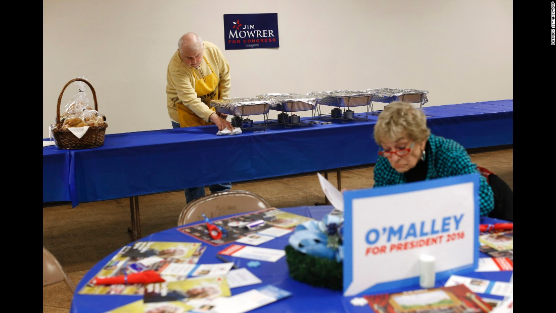 Ray Blase prepares a dinner service as Shirley Evans reads political brochures before political candidates speak in Des Moines, Iowa, on Thursday, January 14.