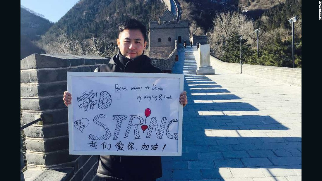 """Feng Chen, Xu's business partner, also posed with the """"#DStrong"""" sign, which he drew."""