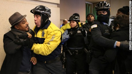 Protesters scuffle with police outside the hotel where the breakfast took place.