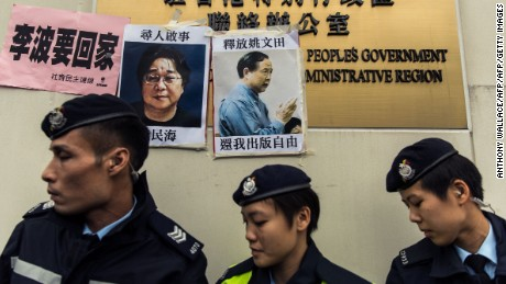 Police walk past missing person notices of Gui Minhai (L) and Yau Wentian (R)