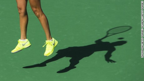 A tennis player's shadow spreads across the court as she jumps to reach a shot.