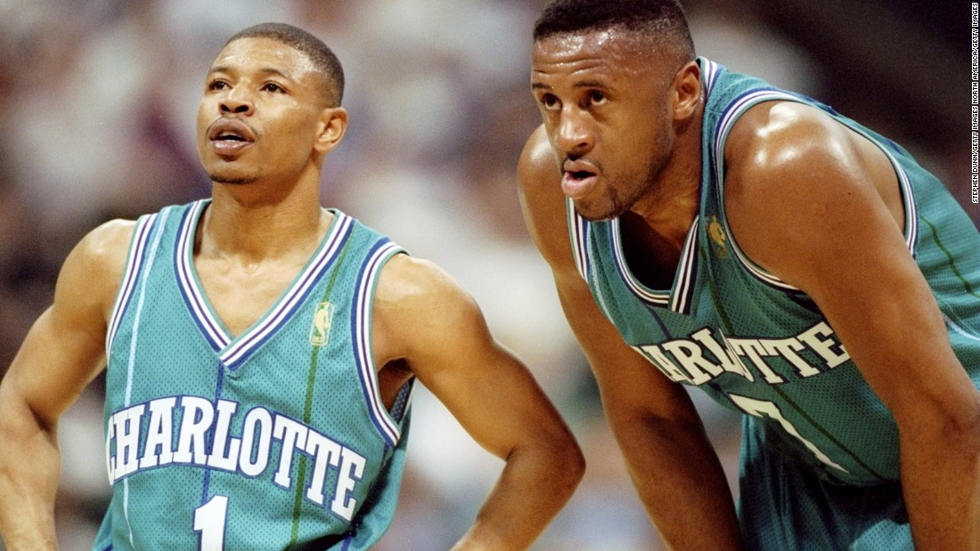 "At 5 feet 3 inches tall, Tyrone ""Muggsy"" Bogues is the smallest player in NBA history. Here, 6-feet-7-inch forward Rafael Addison stoops to Muggsy's level during a game against the Dallas Mavericks in Texas in 1997."