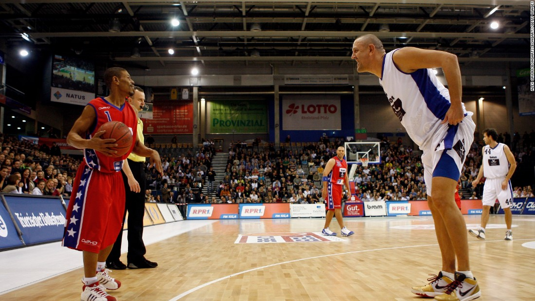 "David meets Goliath: Muggsy holds the ball during an exhibition game between the ""USA Legends of Basketball"" and a Germany/Luxemburg All Star team in 2009. Bogues was greeted with incredulity wherever he went. Today, he's remembered as a legend."