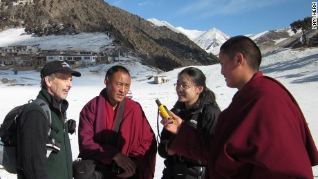 Tom McCarthy, left, executive director,  Panthera Snow Leopard program and Yin Hang formerly of Chinese NGO Shan Shui, second right, discuss snow leopard monitoring methods with Buddhist monks.