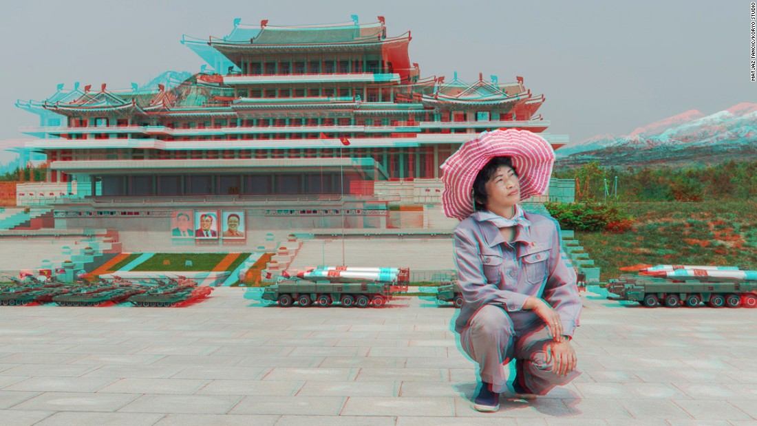 """This was taken at a park in Pyongyang where they have [famous] sites but in miniature. This lady took care of the greenery in the area. I asked her to stand up next to the miniature library. But she said she could not have her photo taken with her higher than the leaders in the photo. So I asked if she could kneel down, and she said yes."""