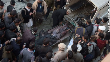 People gather around as policemen move the bodies of Taliban militants.