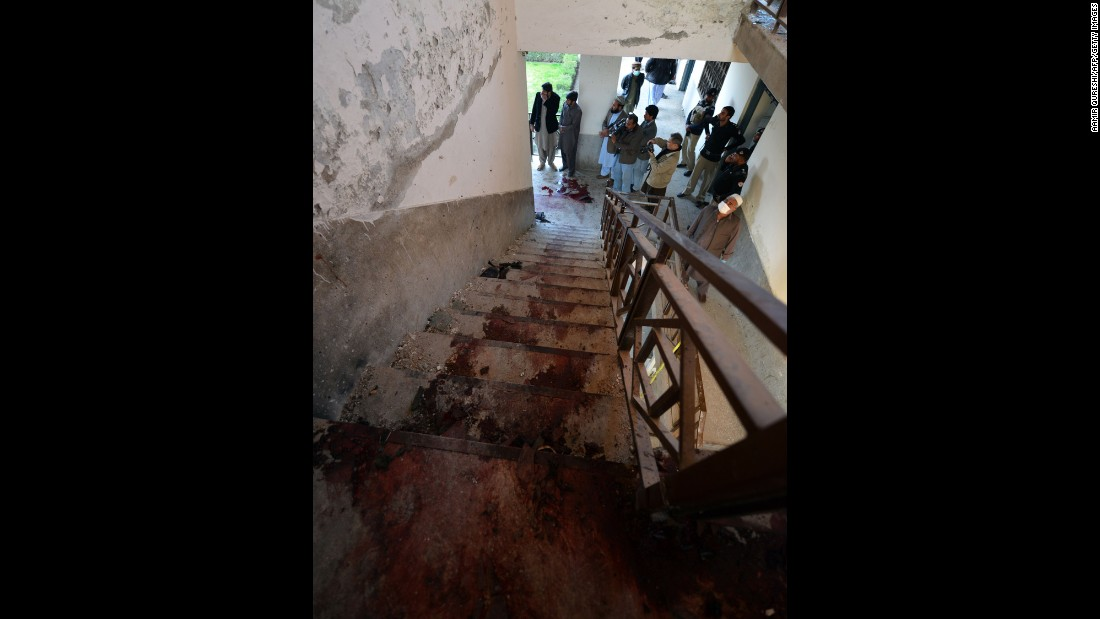 Policemen stand at the bottom of stairs splattered with blood where militants were killed.