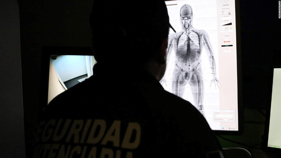 An officer operates the body scan machine.