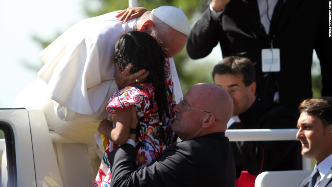 Pope Francis embraces a little girl named Sophie after she breached security and ran towards him during a parade in Washington last September.