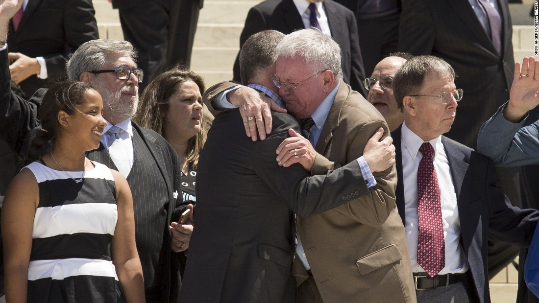 Jim Obergefell, in dark suit,  hugs fellow plaintiff Luke Barlowe as they exit the Supreme Court after oral arguments in their case last April in Washington. Two months later, the Supreme Court ruled that same-sex marriage is a constitutional right.