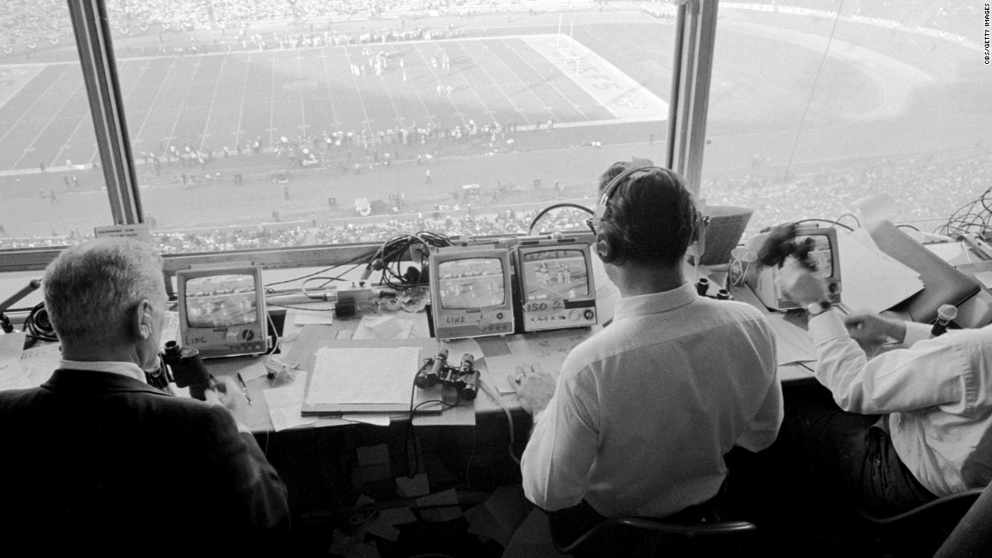 The CBS Sports team works in the press box during the game.