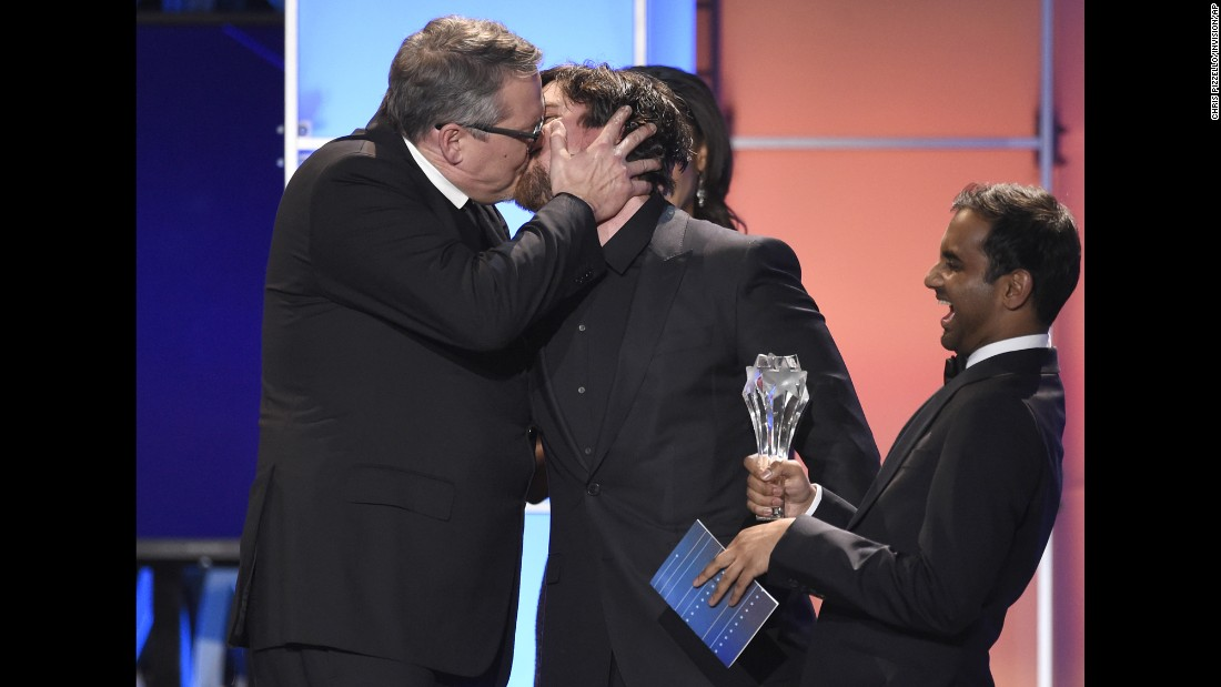 "Director Adam McKay, left, kisses actor Christian Bale after their movie ""The Big Short"" won the Critics' Choice Award for best comedy on Sunday, January 17. Holding the award is presenter Aziz Ansari."