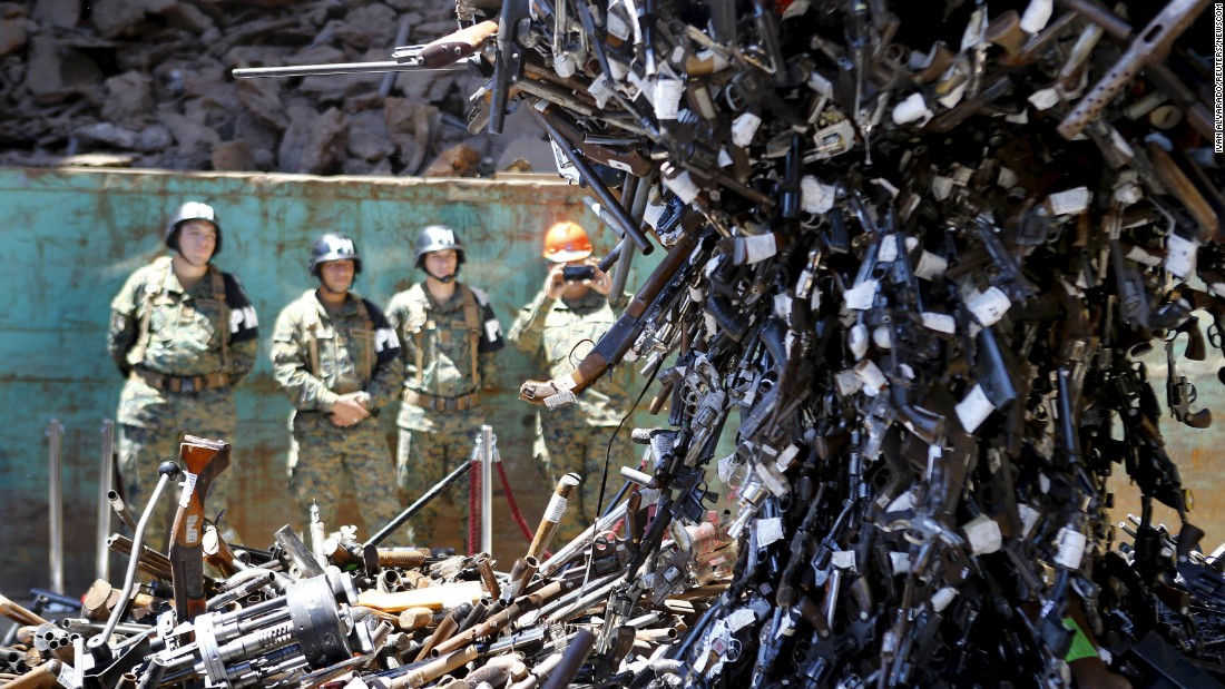 Confiscated weapons hang from a magnet before being destroyed at a foundry in Santiago, Chile, on Monday, January 18. Nearly 13,000 firearms were destroyed as part of a government arms-control program.
