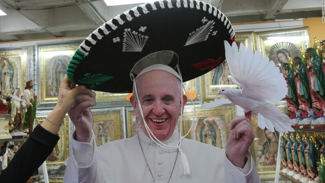 A woman puts a sombrero on a Pope Francis figure in Mexico City on Tuesday, January 19. The Pope is visiting Mexico next month.