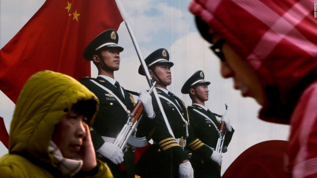 People in Beijing walk past a poster of the Chinese army on Thursday, January 21.