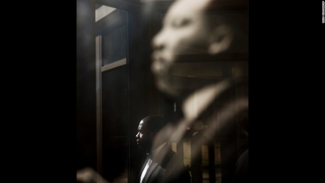 A man in Atlanta is reflected in glass at Ebenezer Baptist Church while he walks past a photo of Martin Luther King Jr. on Monday, January 18. The civil rights icon used to preach at the church.