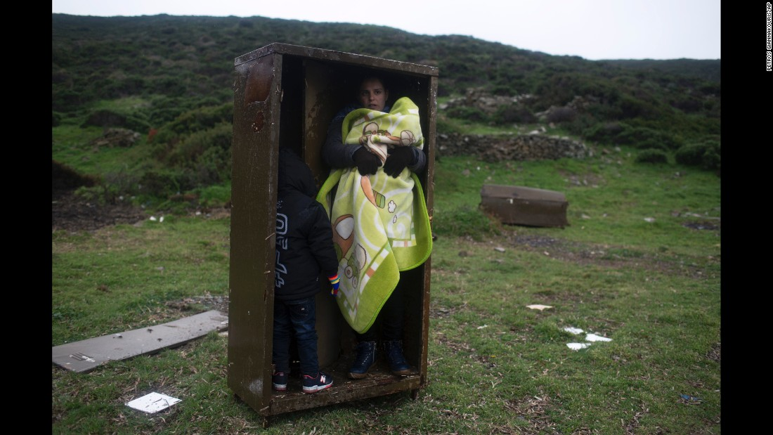 A Syrian refugee and her children take shelter in an iron box, protecting themselves from the rain after they arrived on the Greek island of Pasas on Wednesday, January 20.