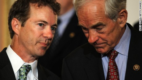 U.S. Sen. Rand Paul (R-KY) (L) talks to his father Rep. Ron Paul (R-TX) (R) during a news conference June 22, 2011 on Capitol Hill in Washington, DC.