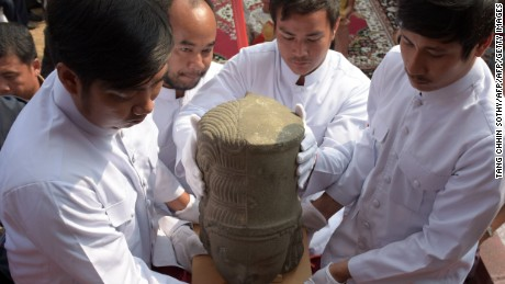Museum employees carry the head of the Harihara statue during a ceremony connecting the head to the body.