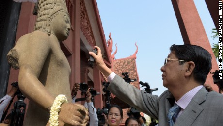Cambodian Deputy Prime Minister Sok An sprays perfume on a depiction of the Hindu deity Harihara during a ceremony connecting the statue's head to its body at the National Museum in Phnom Penh on January 21, 2016.