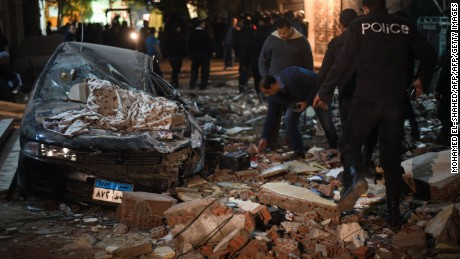 Damaged cars are seen at the scene of a bomb blast in Giza on January 21, 2016.