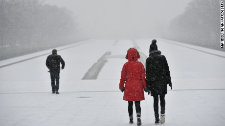 Visitors walk under snowfall on the National Mall, in front of the Lincoln Memorial, on January 22, 2016, in Washington, D.C.