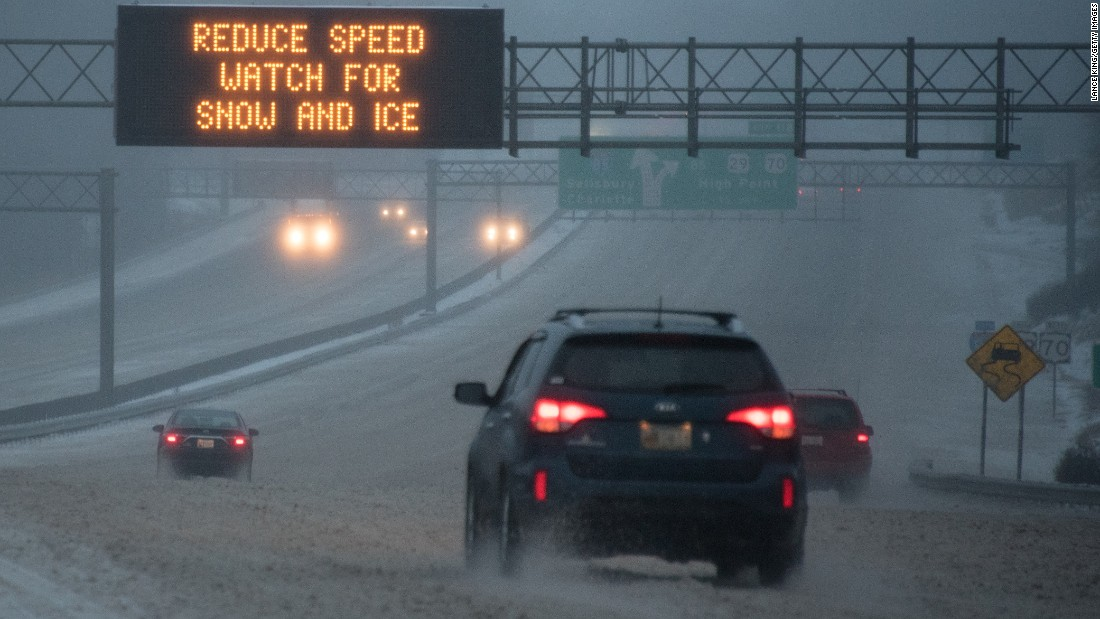 Vehicles move along Interstate 85 as a sign warns about adverse conditions in Greensboro, North Carolina, on January 22.