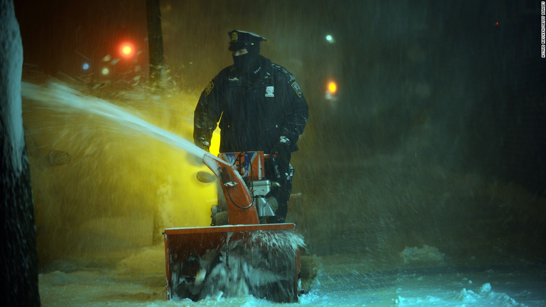 A New York City police officer uses a snow blower to clean the sidewalks on January 23.