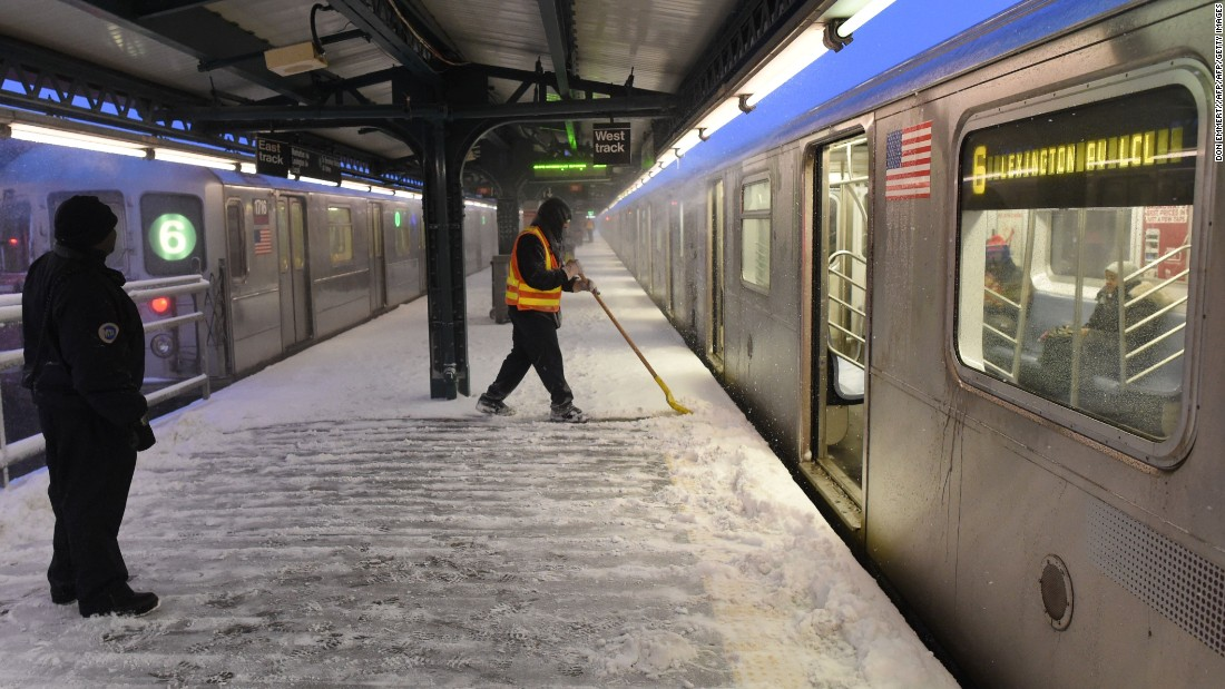 A New York City transit worker shovels snow from a subway platform on January 23.