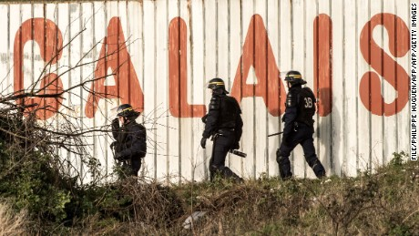 "TOPSHOT - French riot police officer walk in front of a fence with the lettering 'Calais' near the A16 motorway near the site of the Eurotunnel in Coquelles, near Calais, northern France on January 21, 2016. Approximately 300 migrants have tried to board trucks protected by French police, according to an estimate made by an AFP photographer present at the scene. Clashes already erupted briefly on the night of January 20 at the port bypass Calais between several hundred migrants and security forces, who fired tear gas to restore the situation, according to an AFP correspondent. These incidents occurred after the prefecture of Pas-de-Calais had set an ultimatum which expired early in the afternoon for the last migrants to leave a deforested 100 metre strip of the ""Jungle"" camp along the ring road for safety reasons. / AFP / PHILIPPE HUGUEN        (Photo credit should read PHILIPPE HUGUEN/AFP/Getty Images)"