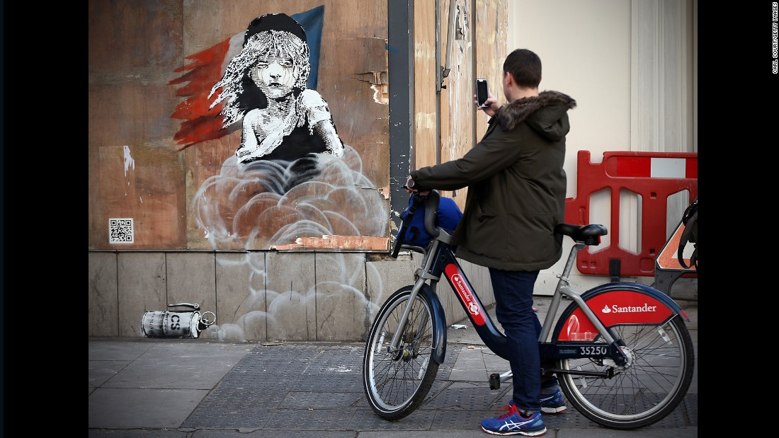 The image, near the French Embassy in London, depicts the character Cosette from the musical Les Miserables as a refugee. It follows reports that French authorities used teargas and rubber bullets to clear sections of the camp earlier this month. An interactive QR code links visitors to a video of the clearance.