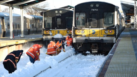 Workers clear train tracks of snow at the Port Washington station on the Long Island Railroad in Port Washington, New York, on Monday, January 25.