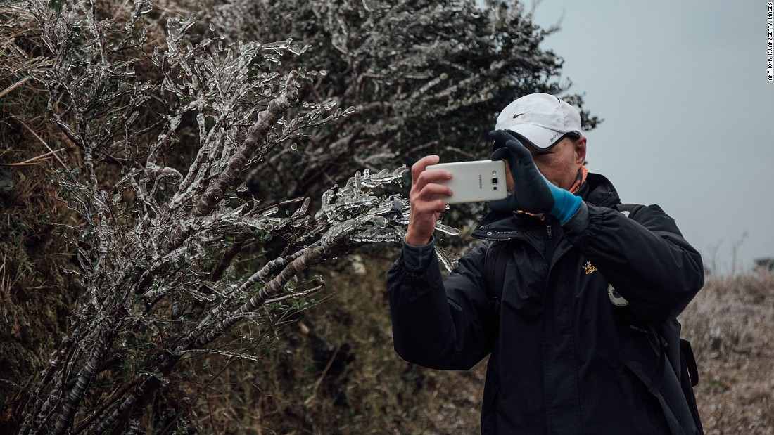 A hiker takes a photo of a frozen plant in sub-zero temperatures atop Hong Kong's highest peak on Sunday, January 24. Temperatures plunged to the lowest point in 59 years and frost dusted the mountaintops of a city accustomed to a more subtropical climate.