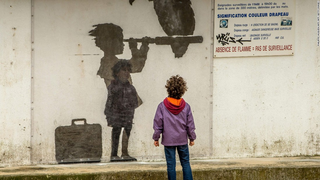 A third image which appeared by the coast  shows a child with a suitcase looking through a telescope, which has a vulture perched on top of it.