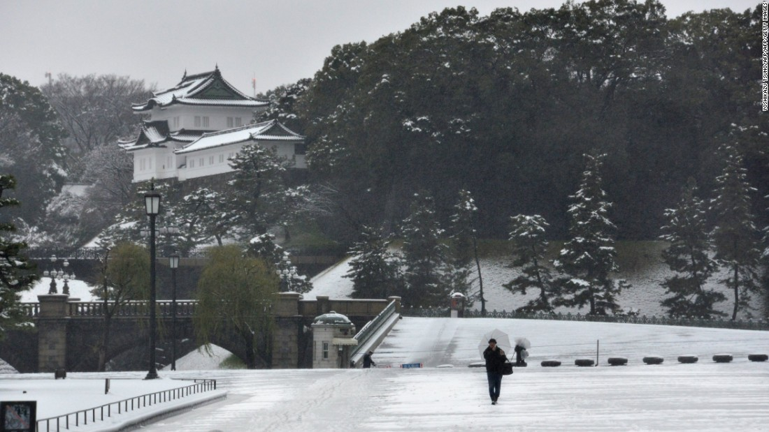 A man walks on a snow covered field in front of the Imperial Palace in Tokyo on January 18. The Amami Oshima island, located in the country's southern Kagoshima prefecture, saw snow for the first time in 115 years.