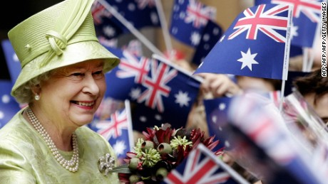 Britain's Queen Elizabeth II (L), receives flowers from waiting school children waiving national flags after the Commonwealth Day Service in Sydney, 13 March 2006.  Britain's Queen Elizabeth II began the first official function of her 15th visit to Australia with a visit to Sydney's harbour she described as rich in memories and symbolism.   AFP PHOTO/Rob GRIFFITH/POOL (Photo credit should read ROB GRIFFITH/AFP/Getty Images)