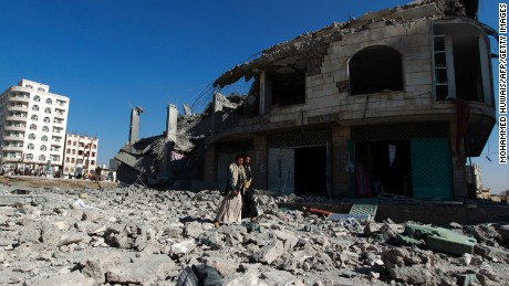 Yemenis walk past the site of a Saudi-led airstrike that targeted a building in Sanaa, Yemen.