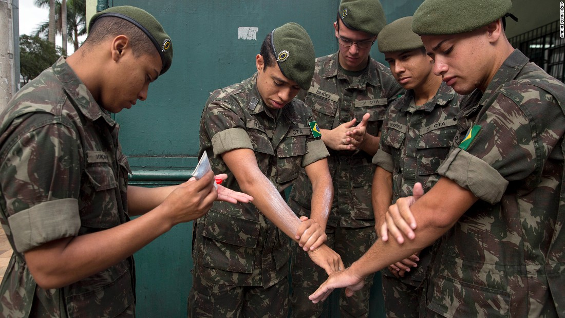 Brazilian soldiers apply insect repellent as they prepare for a cleanup operation in Sao Paulo on Wednesday, January 20.