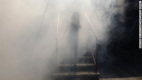 A woman walks through a haze of pesticide in  El Salvador.