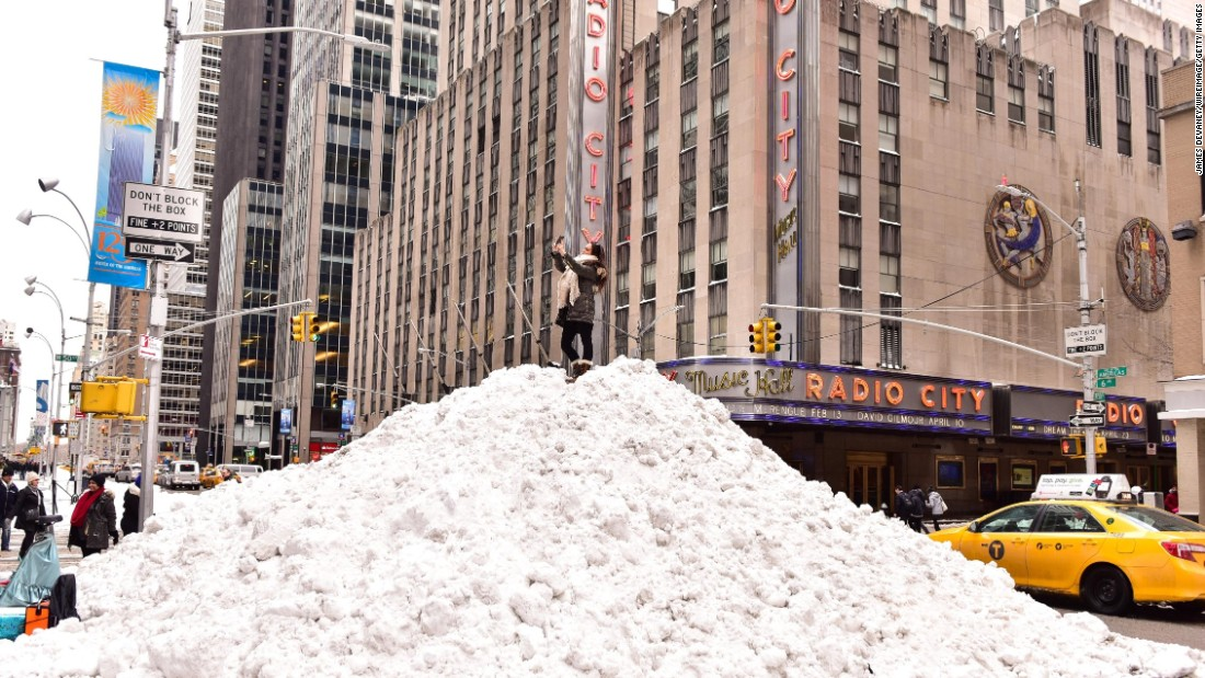 A woman in New York takes a selfie on top of a snow pile outside Radio City Music Hall on Sunday, January 24.
